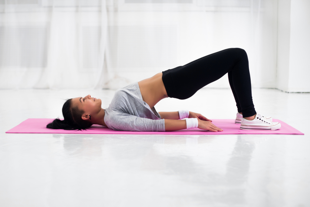 Bridge pose sporty woman doing warming up exercise for spine, backbend, arching stretching her back  working out at home fitness workout yoga gymnastics concept
